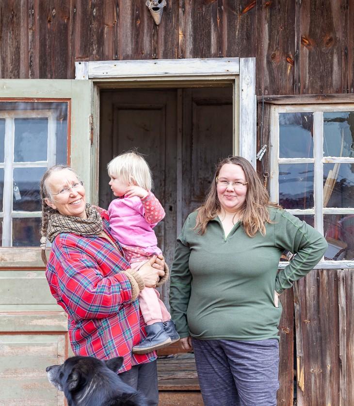 Sanna Sinisammal sylissään Inka-tyttö sekä Selma Kilpi talon portailla Tärkkilän ekokylässä.